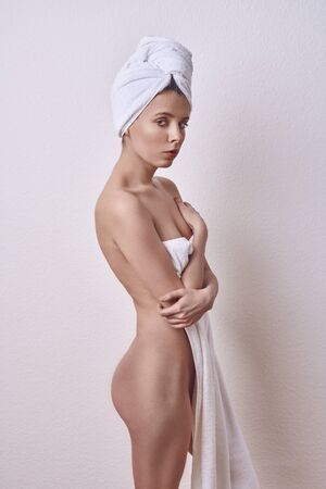 Alluring young  woman covering her breasts and front of her torso with a fresh clean white a towel as she looks at camera with a sultry expression and parted lips over a white studio background