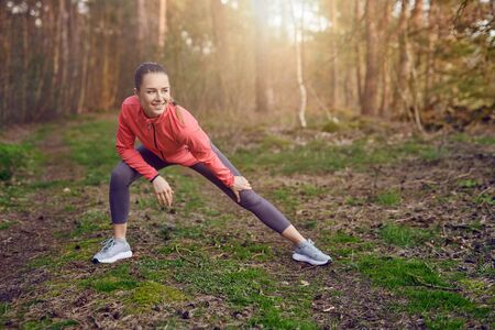 Full length portrait of a happy  fit young woman doing stretching exercises for legs and arms during outdoor workout in the forest in Springtime