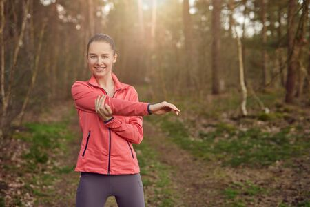 Front view portrait of a happy fit woman stretching her arm during warming up exercises outdoors in the forest in Springtime Фото со стока