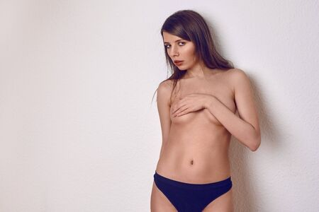 Topless sexy young brunette woman in blue panties covering her breast with one hand, standing on light background in studio and looking at camera with seductive look. Front portrait with copy space Фото со стока