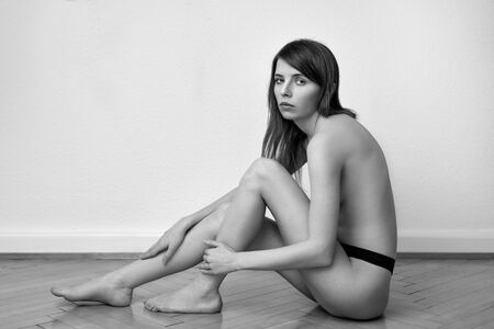Alluring topless young woman posing in her panties sitting on a herringbone parquet floor in side view looking quietly at the camera with a serious expression in black and white monochrome