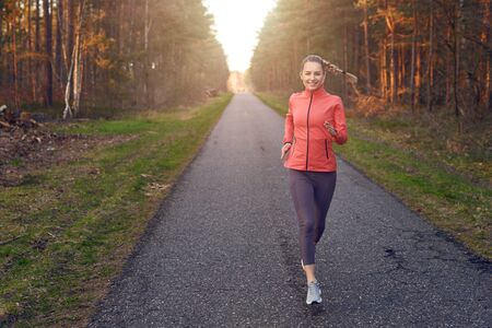 Young fit woman runinng on a tar track through the forest in the sunset glow of sunlight with copy space to the left Фото со стока
