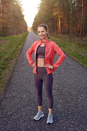 Full length front portrait of sporty young girl in training wear with grey pants and red jacket, standing and resting after jogging with her hands on hips, looking at camera and smiling Фото со стока