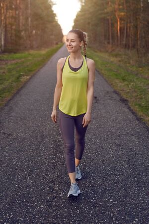Smiling athletic fit young woman working out on a tarred lane through forests backlit by the warm glow of the sun in a healthy active lifestyle concept