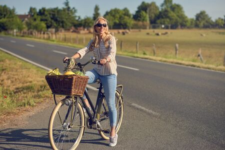 Middle-aged blond woman shopping for groceries on her bicycle stopped at the side of the road with a basketful of healthy fresh produce smiling as she faces into the spring sunshine in a rural landscape