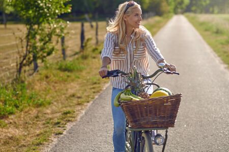 Happy woman smiling while riding a bicycle with a basket full of fresh and healthy fruits in a sunny day of summer in the countryside Фото со стока