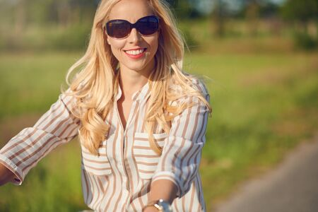 Portrait of a beautiful woman smiling happy while wearing a striped shirt and riding a bicycle in the countryside in a sunny day