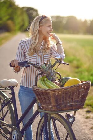 Woman using her bicycle to buy fresh produce standing on a rural road backlit by a warm glow of the sun smiling happily at the camera as she holds her bike with basket full of fruit and vegetables Фото со стока