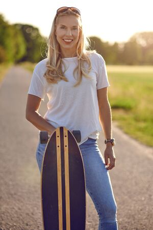 Portrait of a fit beautiful middle-aged woman with an active lifestyle smiling and looking at camera while holding a longboard on a sunny road in the park in summer
