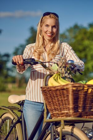 Woman using her bicycle to buy fresh produce standing on a rural road in the warm glow of the sun smiling happily at the camera as she holds her bike with basket full of fruit and vegetables