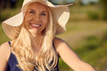 Attractive friendly smiling blond woman with long hair wearing a straw sunhat outdoors on a summer day in a close up portrait