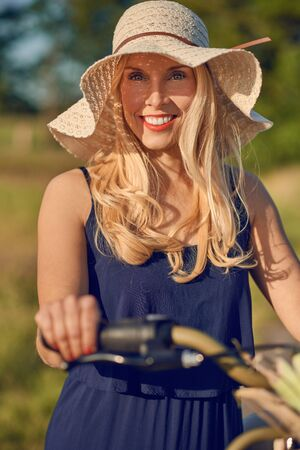 Attractive blond woman with lovely friendly smile standing outdoors with her bicycle in the spring sunshine wearing a broad brimmed straw sunhat