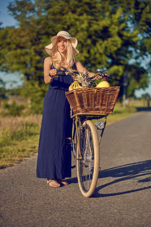 Attractive woman wearing a broad brimmed straw sunhat shopping for fresh produce in the country wheeling her bicycle along a rural lane in warm evening light in a close up portrait