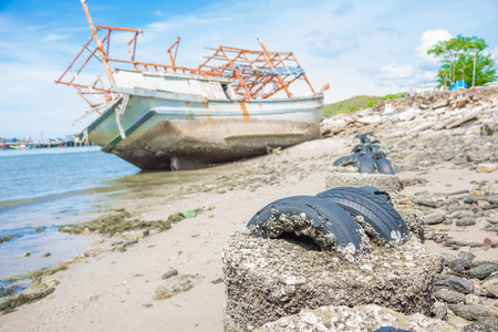 ship wreck: barnacle on tire and wreck boat on beach blur background Stock Photo