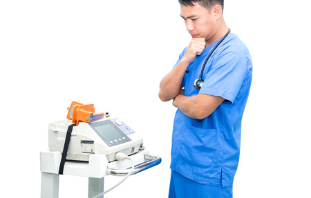 asia doctor stand near EKG monitor and stethoscope on neck isolated Stock Photo