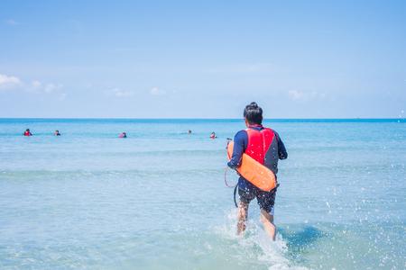 바다에서 희생자를 돕기 위해 달리는 구명 조끼 착용 구명 조끼 스톡 콘텐츠