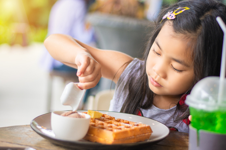 girl pour sweet honey syrup on the pancake Stock Photo