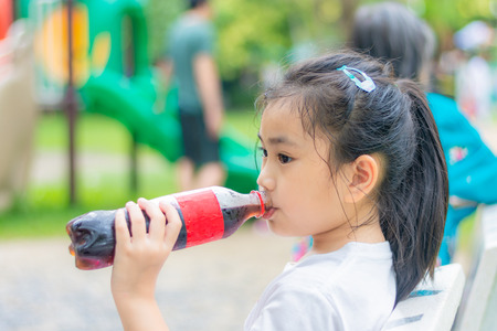 Asia little girl drink water in the garden Stock Photo
