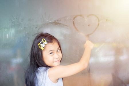 asia little girl writing heart on glass