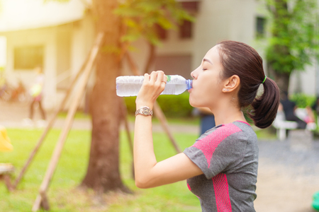 asia sport girl drinking water in the garden after running exercise Stock Photo