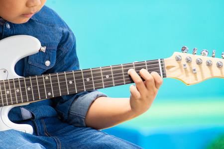 asia young boy playing guitar filling funny