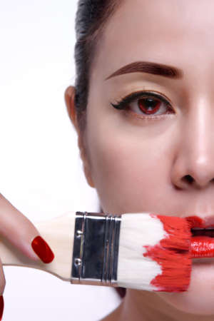 Asia women model with red nails lips and brush red color Standard-Bild