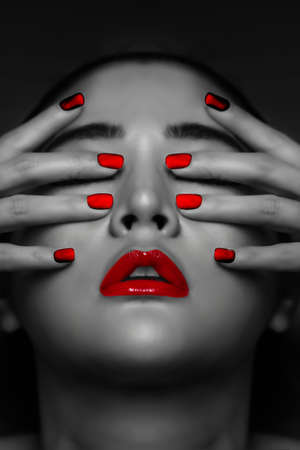 Asian woman with red nails and red lips dark tone