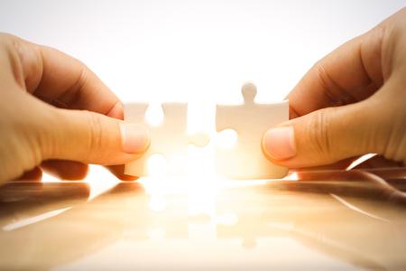 Frauenhand, die Puzzles hält und verbindet. Geschäftslösungen, Verbindung, Leistung und Strategiekonzept