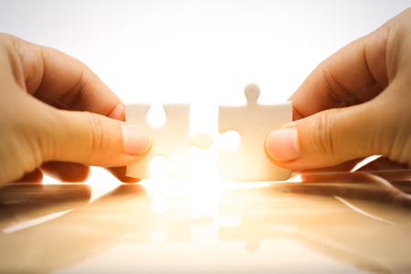 Woman's hand holding and connecting jigsaw puzzles. Business solutions, connection, achievement, and strategy concept