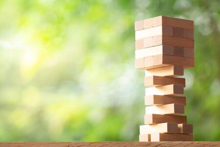 Tour de pile en bois à partir de blocs de bois jouet sur fond flou de verdure avec espace de copie. Concept de stratégie d'entreprise, de construction, d'inclinaison et de développement