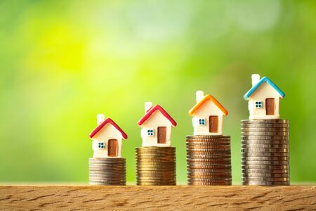 Four miniature house models on coin stacks on greenery blurred background with copy space. Business, finance, and saving money for dream house concept Stockfoto