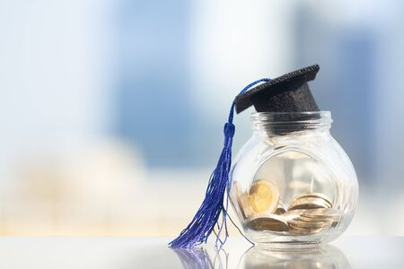 Graduation hat with blue tassel on top of glass jar or piggy bank filled with coins on modern city background with copy space. Saving money for education or scholarship concepts