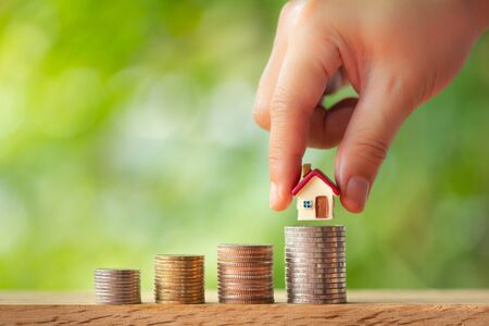 Hand putting house model on coin stacks on greenery blurred background. Saving money for dream house concept Stockfoto