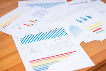 Business report with variety of graphs and charts on desk. Business and finance background concept.