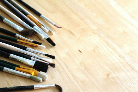 Mixed artists paint brushes on pine table with space Stock Photo - 9844169