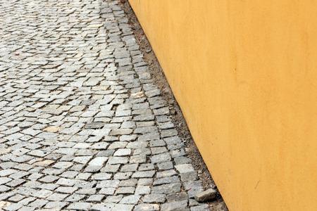 empedrado: Pared amarilla y calle pavimentada piedra de la calzada