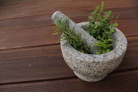 traditional healer: Healthy and fragrant herbs in a stone mortar