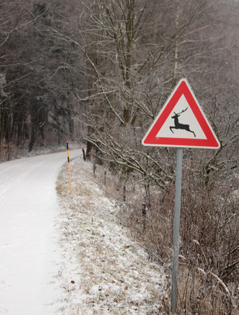 warns: Traffic sign warns about wild animals crossing the winter road Stock Photo