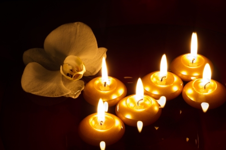 candles in dark: Floating candles and orchid in dark - spa concept