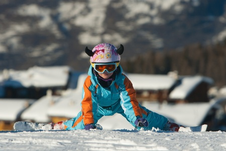 Little girl on her knees  in a ski resort photo