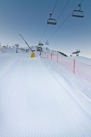 Freshly prepared ski slope with chair lifts