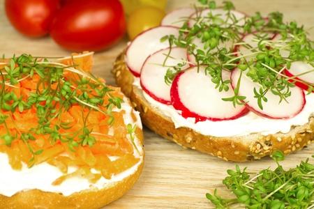 Two vegetarian sandviches - cream cheese, radishes or carrots, watercress on a wholegrain bun