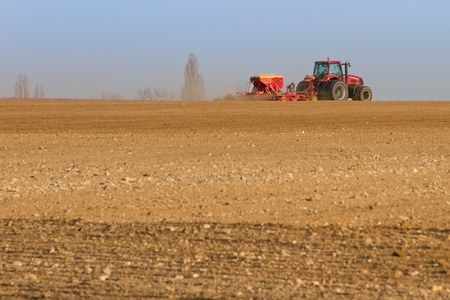 Agriculture tractor sowing seeds and cultivating field (focus on tractor) Stock Photo