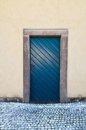 Blue old wooden door, yellow wall and cobblestoned pavement photo