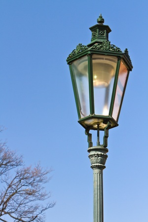 Historic wrought-iron lamp in Prague, Czech Republic  with reflection of red roof