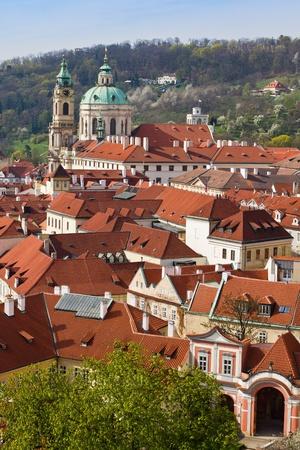 Red roofs in historic Prague, St. Nicholas church and Petrin� hill - Prague, Czech Republic photo