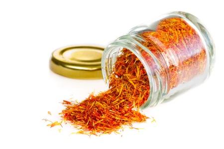 Saffron spice in an open glass jar, on white