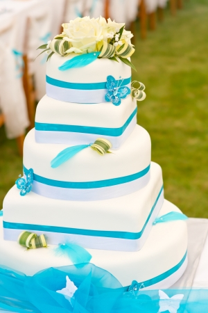 Wedding cake in white and blue combination, adorned with flowers, ribbons and butterflies
