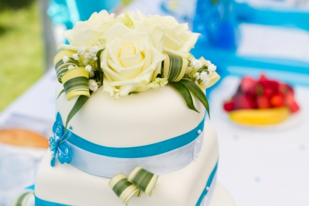 Wedding cake in white and blue combination, adorned with flowers, ribbons and butterflies, focus on flowers photo