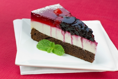 red tablecloth: A piece of forest fruit cake on a square plate and red tablecloth Stock Photo